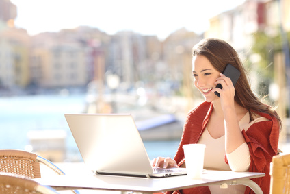 Telefonierende Frau auf Café-Terrasse am Tisch mit Laptop