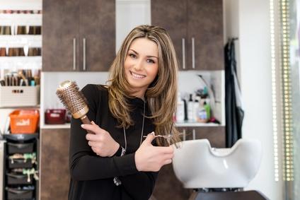 Frisörin posiert mit Bürste und Schere