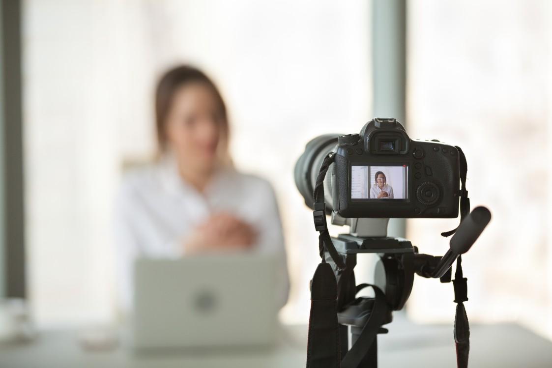 Frau vor Kamera bei Webinar-Livestream